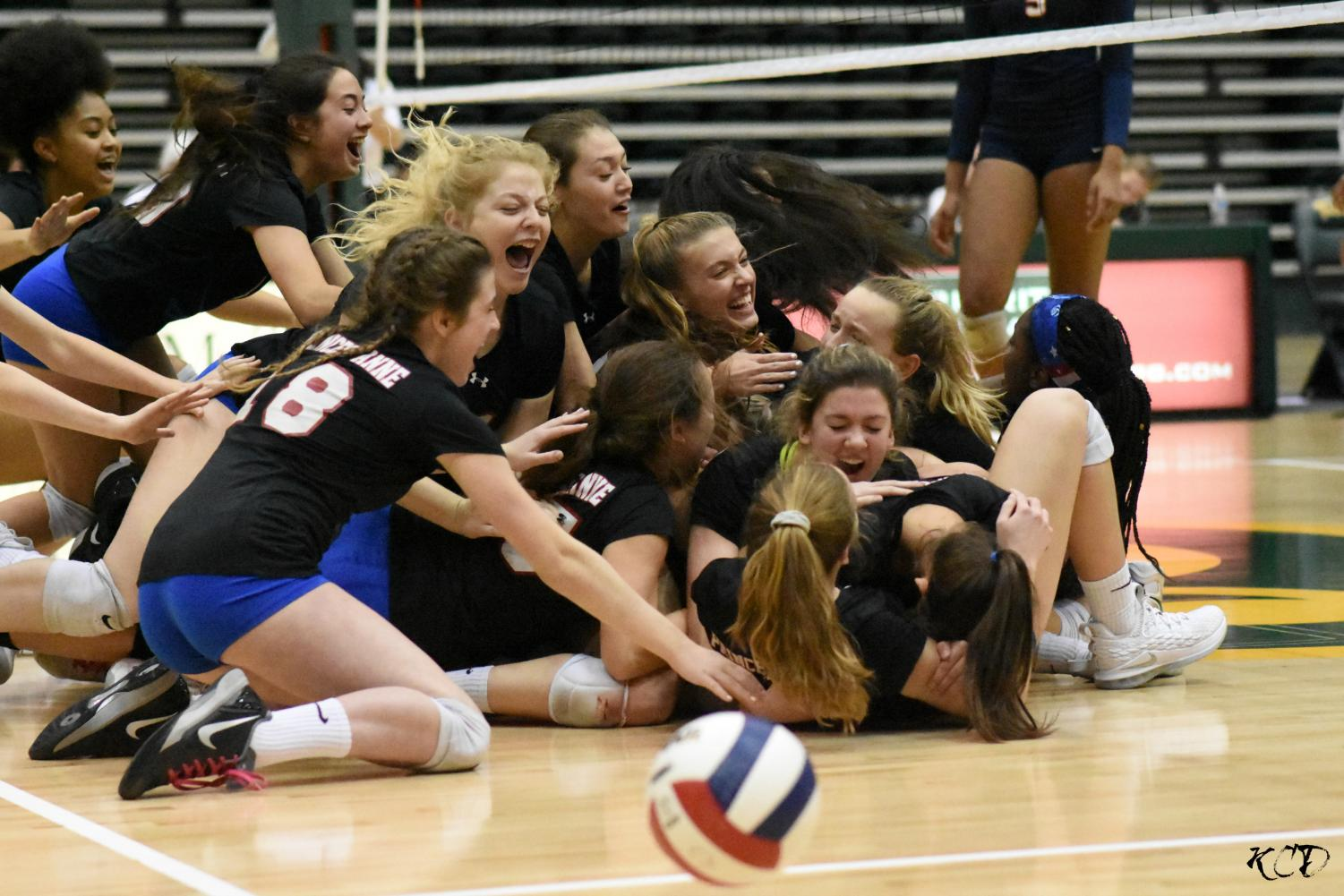 The team piles onto each other after the winning kill. (Photo by Kendra Drew)