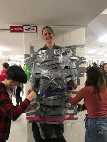 Psychology teacher Kristina Berney being taped to the wall after being chosen by the student body.  Photo by Ekene Osuchukwu.